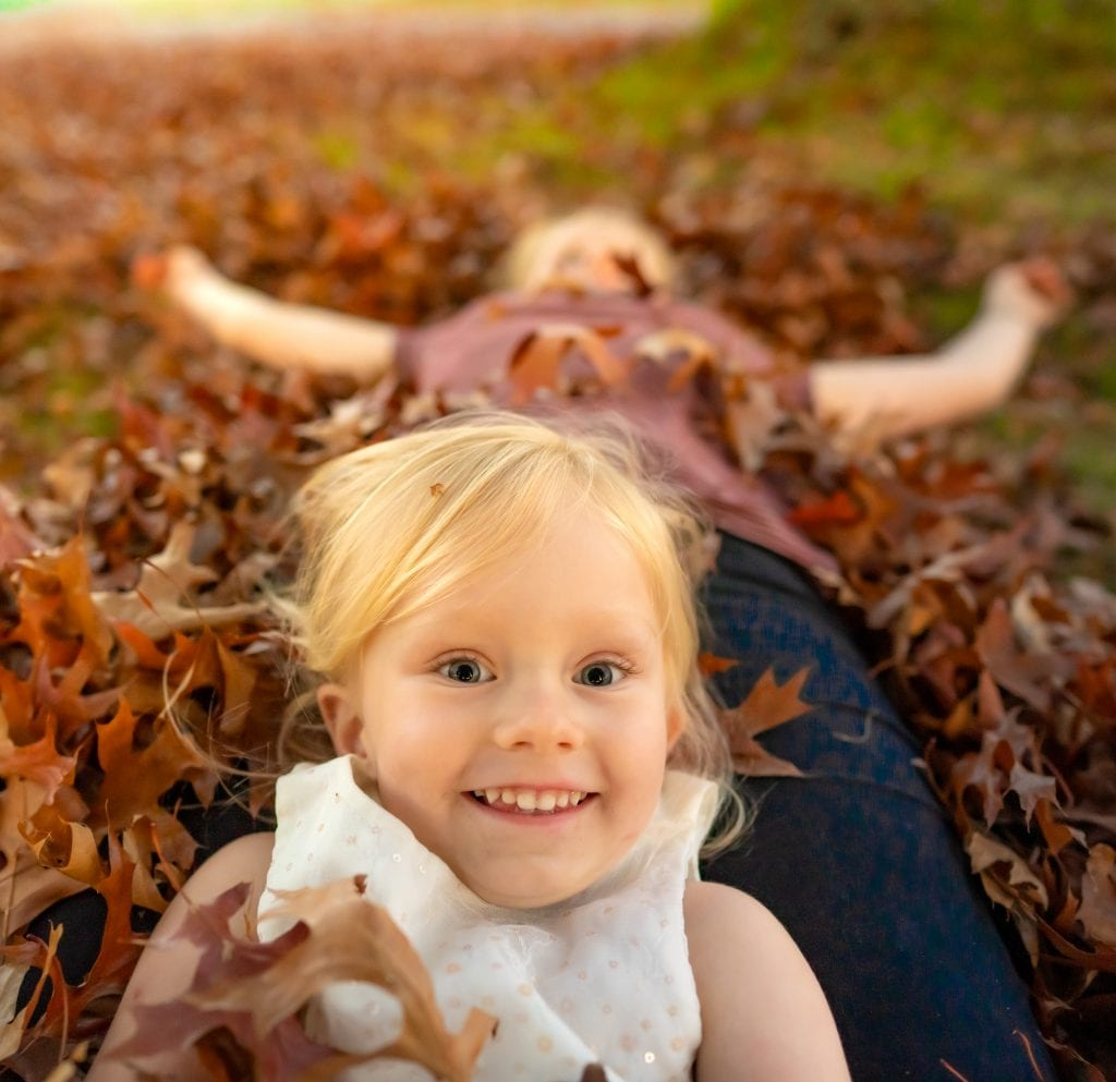 My kids laying in the fall leaves while we quarantine in New Zealand