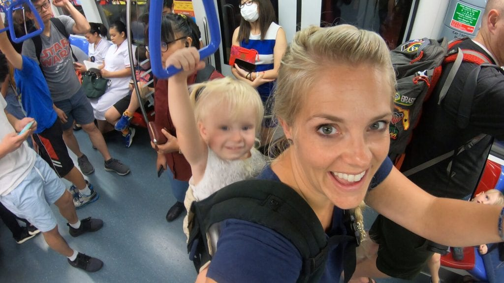 singapore travel guide- my daughter and I on a train while I am carrying her on my back