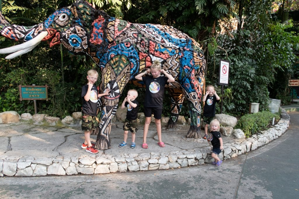 family travel- my kids making sill faces in front of a colorful elephant statue