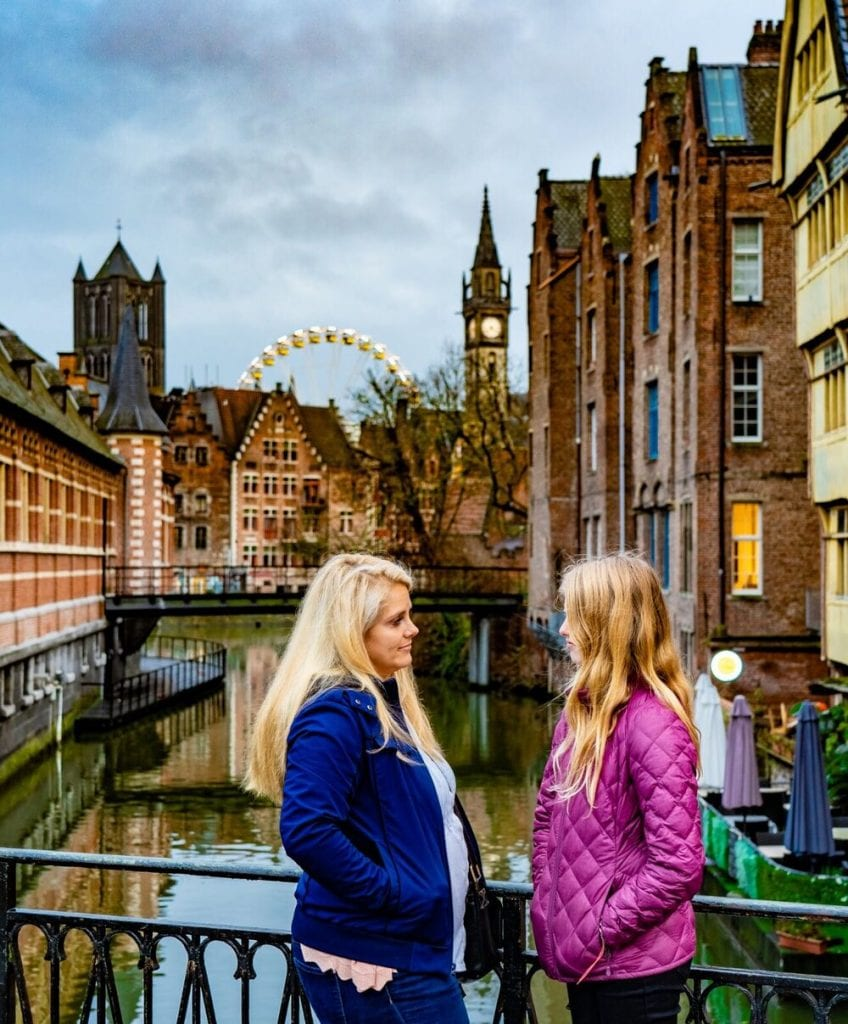 Belgium Trip with Kids: my oldest daughter and I in front of a pretty canal and Ferris wheel
