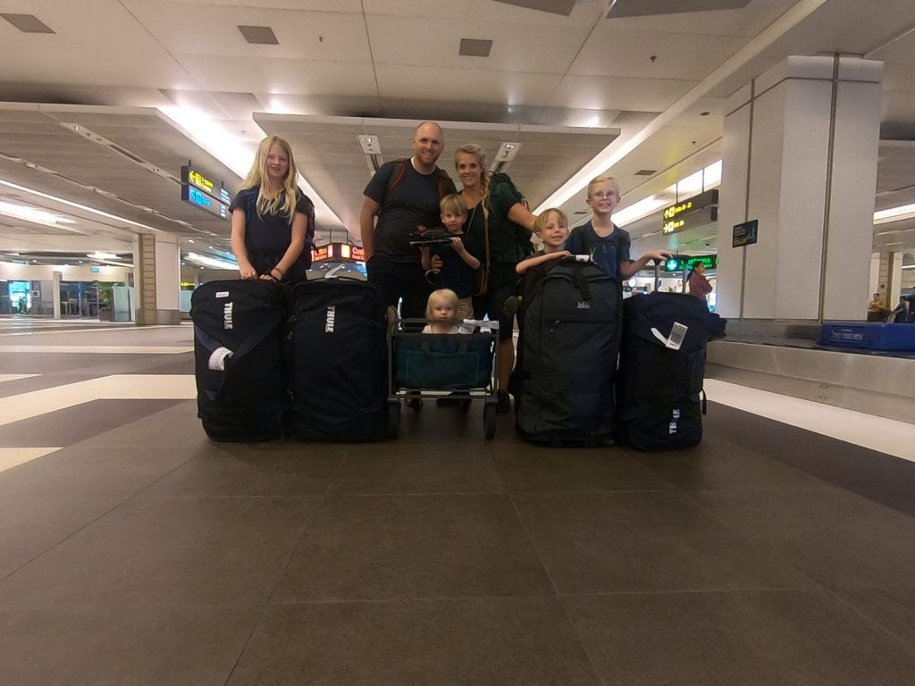 Family picture in the airport with all of our luggage