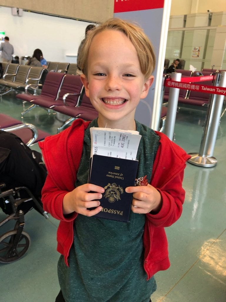 My son smiling with his passport at the airport. Getting new passports is an important step to prepare to travel.