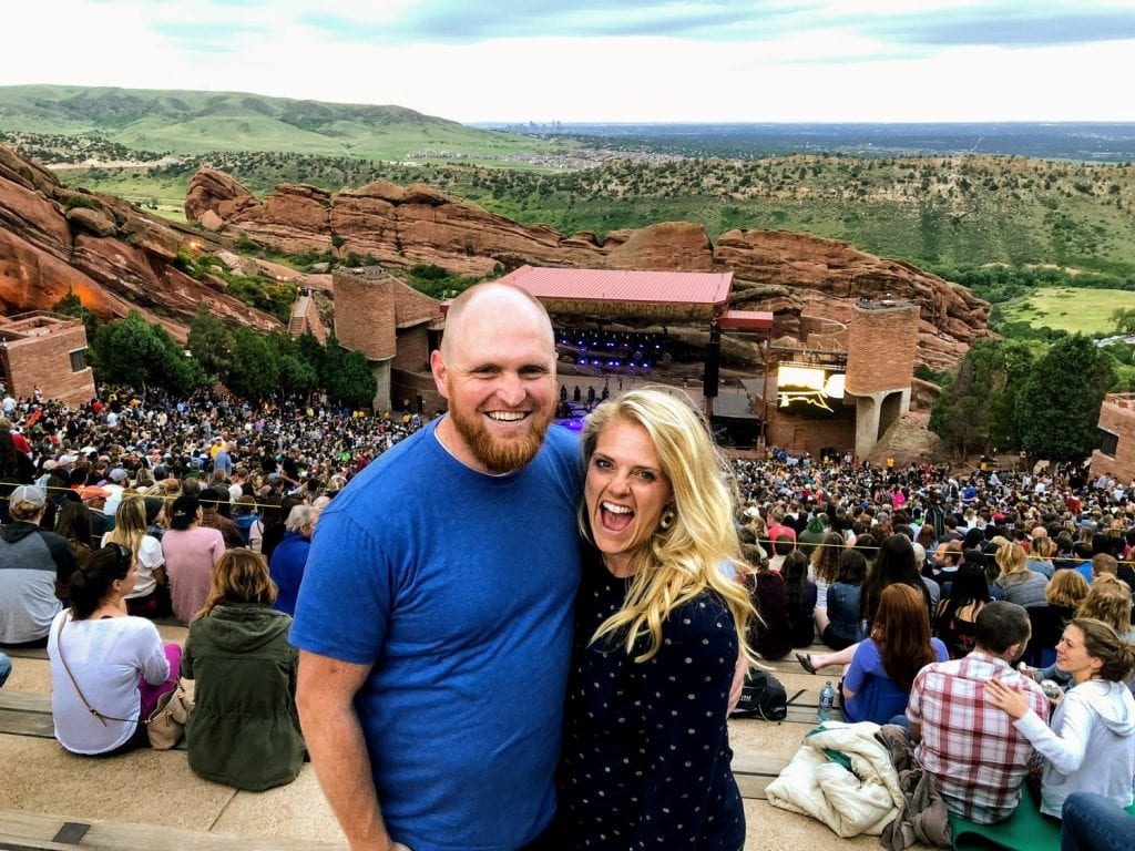 My husband and I at Red Rocks outdoor venue in Colorado on a beautiful sunny day.