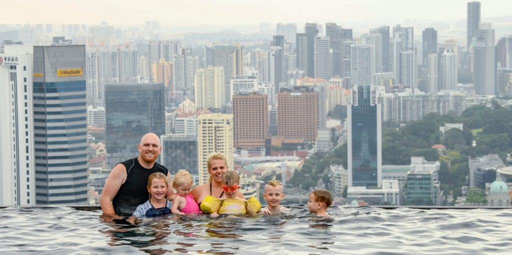 Family photo in Singapore in an infinity pool with the city view