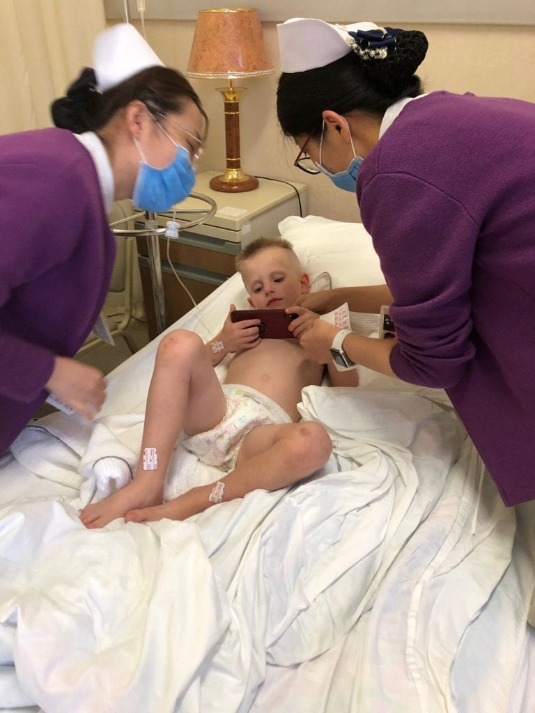 Medical emergency abroad- the nurses talking to Harrison while he laid in the hospital bed playing on a phone