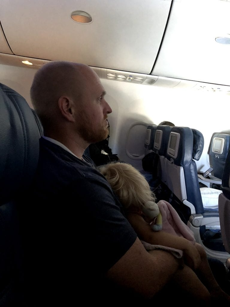 The baby asleep on the airplane while Chris holds her