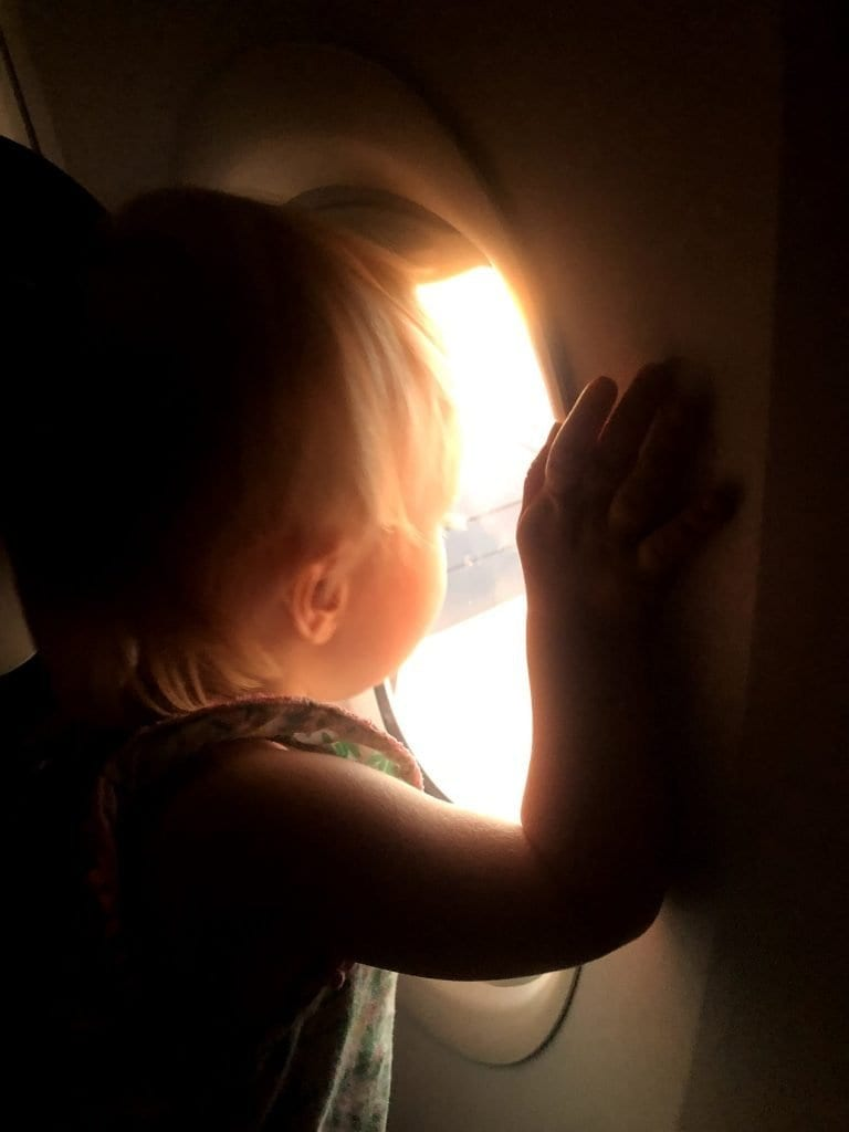 My kid looking out of the window on the airplane