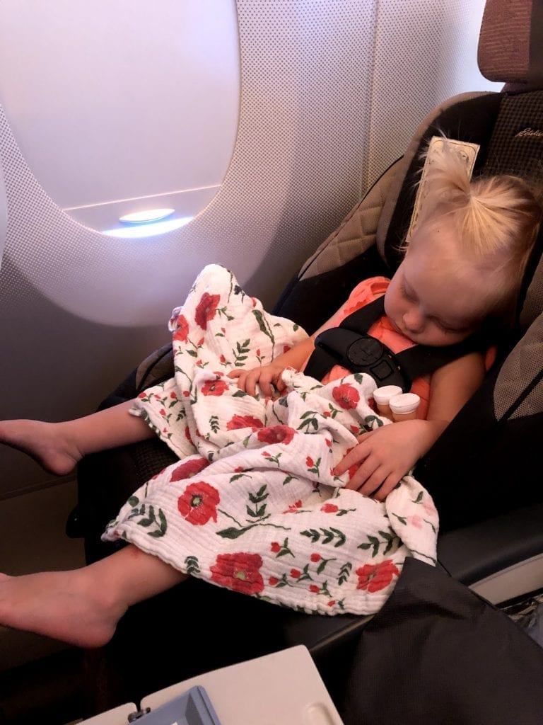 My littlest asleep in her car seat on the airplane