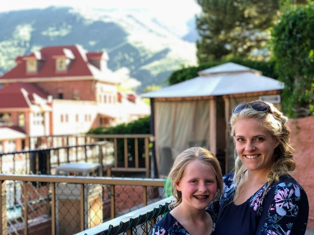 My daughter Lucy and I in matching dresses in front of a sunny mountain view