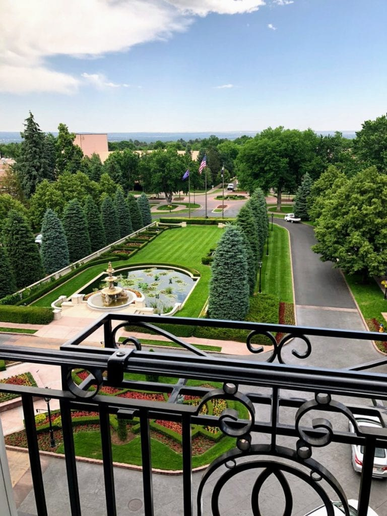 View of the landscaping at the entrance of the Broadmoor-- a fountain and pond surrounded by finely trimmed grass and lined by sculpted trees.