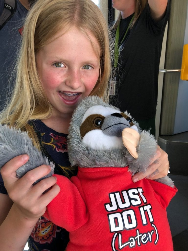 "Lucy and a stuffed sloth wearing a shirt that says ""Just Do It (later)"""