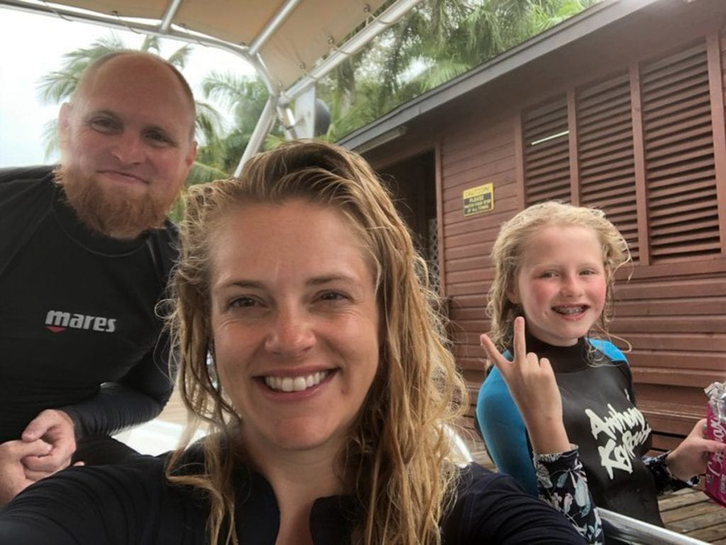 Chris, Leslie, and Lucy in wet suits after a dive