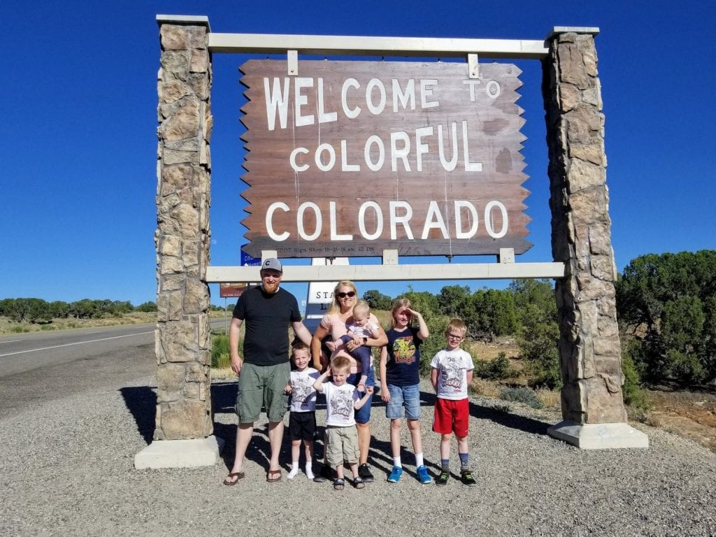 """Or family in front of the """"Welcome to Colorful Colorado"""" sign"""