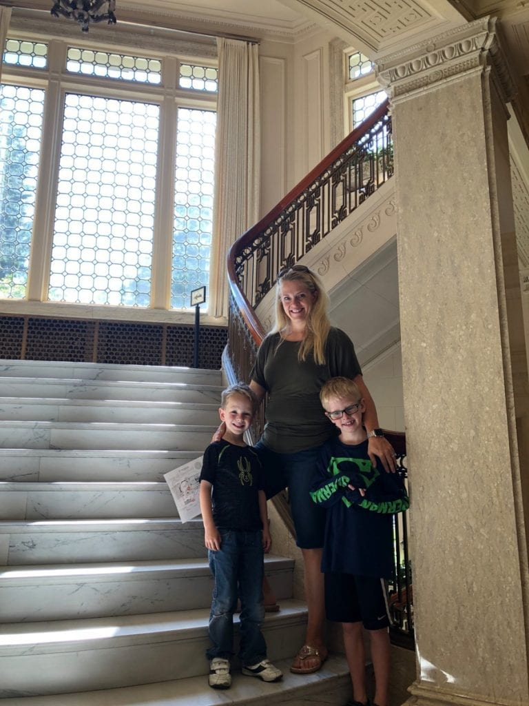 Leslie and the boys standing on one of the mansion's grand stair wells