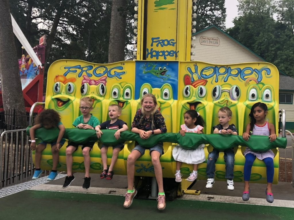 The kids strapped into a rollercoaster called the Frog Hopper