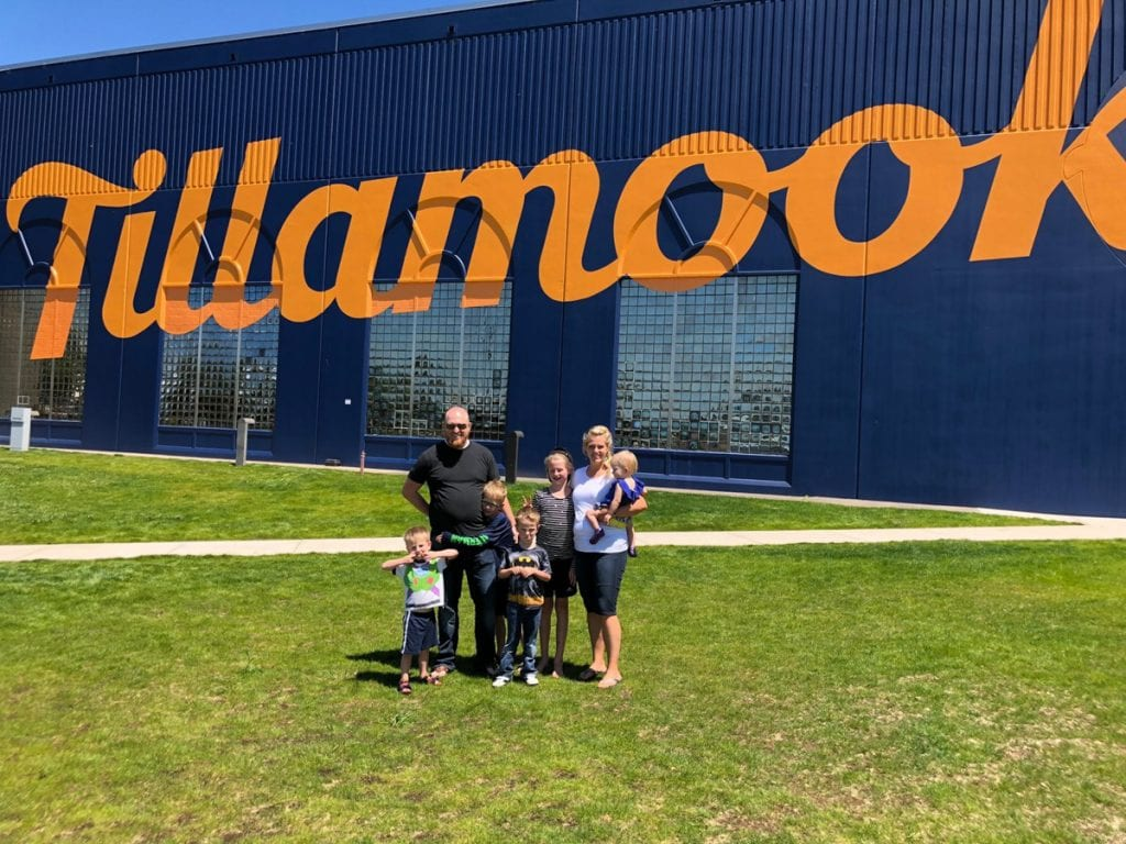 "Family picture outside of the Tillamook factory- a blue building with ""Tillamook"" written in yellow cursive letters."