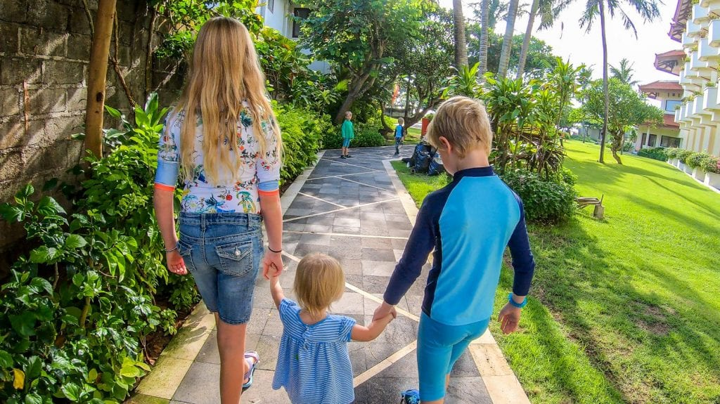 Lucy, Grace. and Grant walking on a sidewalk through palm trees holding hands