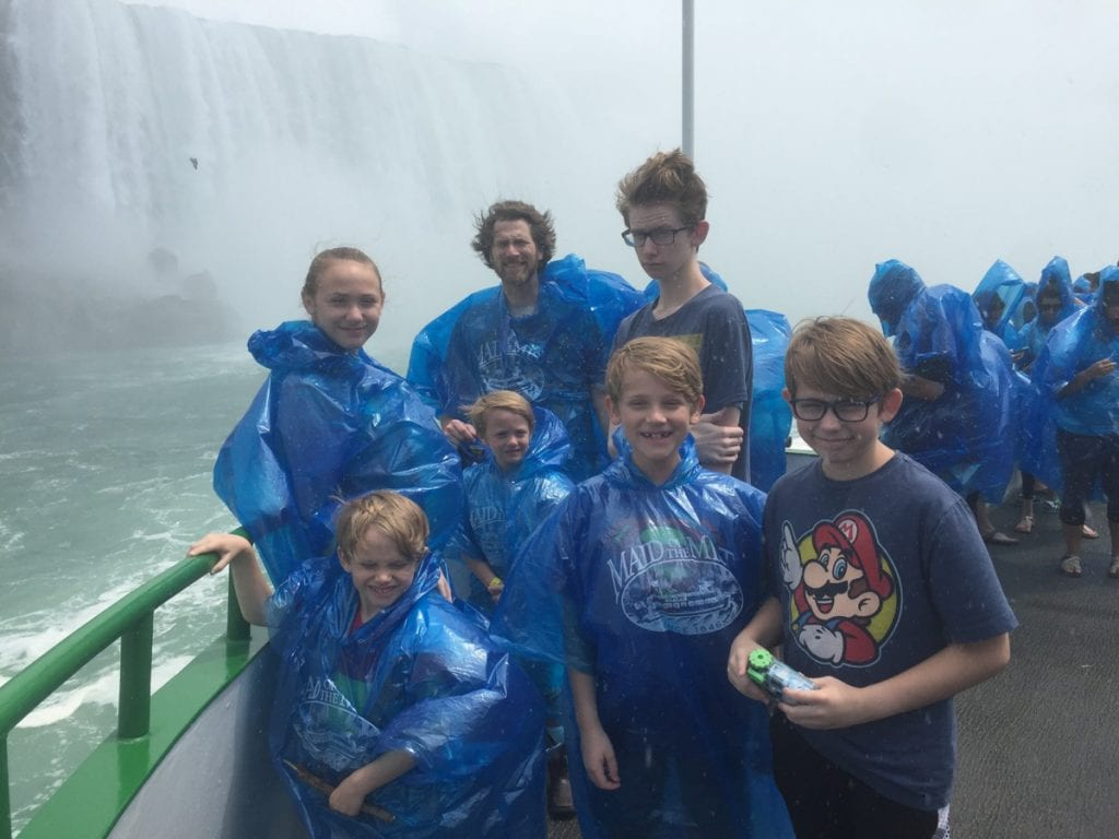The Flory Family in front of a waterfall wearing blue ponchos in foggy weather